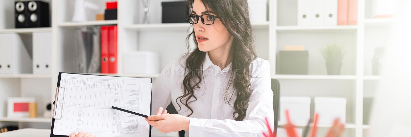 Красивая маленькая девочка сидит на таблице в офисе и указывает карандаш на информацию в документе стоковые фотографии rf