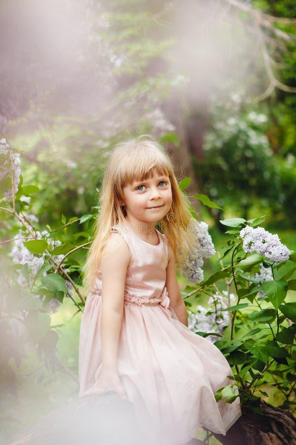 Красивая маленькая девочка сидя и усмехаясь с сиренью цветет вокруг стоковое изображение