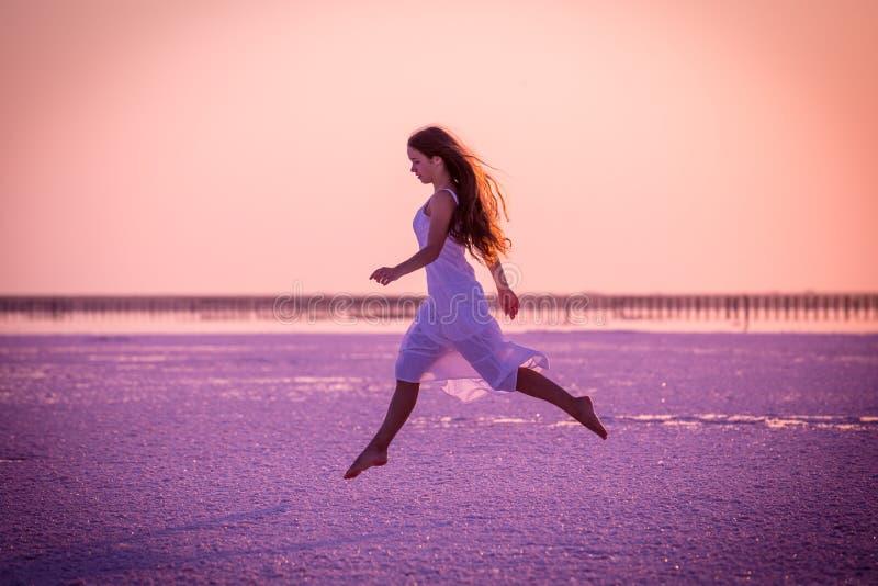 Красивая маленькая девочка скача на озеро соли на заходе солнца стоковая фотография rf