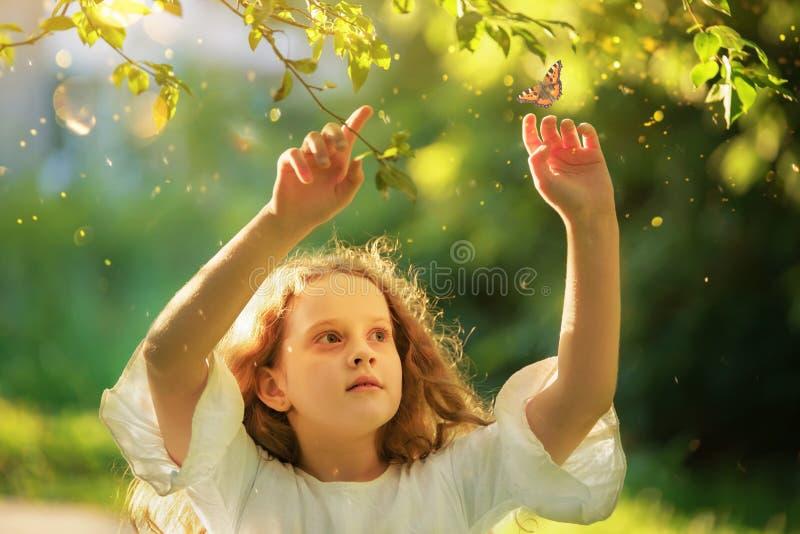 Красивая маленькая девочка смотря бабочку летания в лете su стоковые изображения