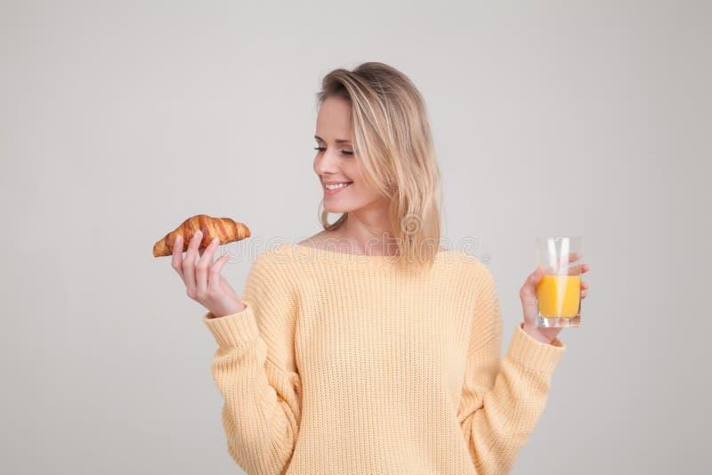 Красивая маленькая девочка со светлыми волосами выпивает апельсиновый сок она одета в желтом свитере r сторона стоковое изображение