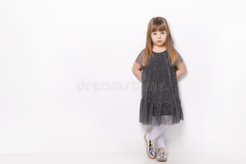 Красивая маленькая девочка со светлыми волосами и голубыми глазами стоя на платье белой предпосылки нося стоковое изображение