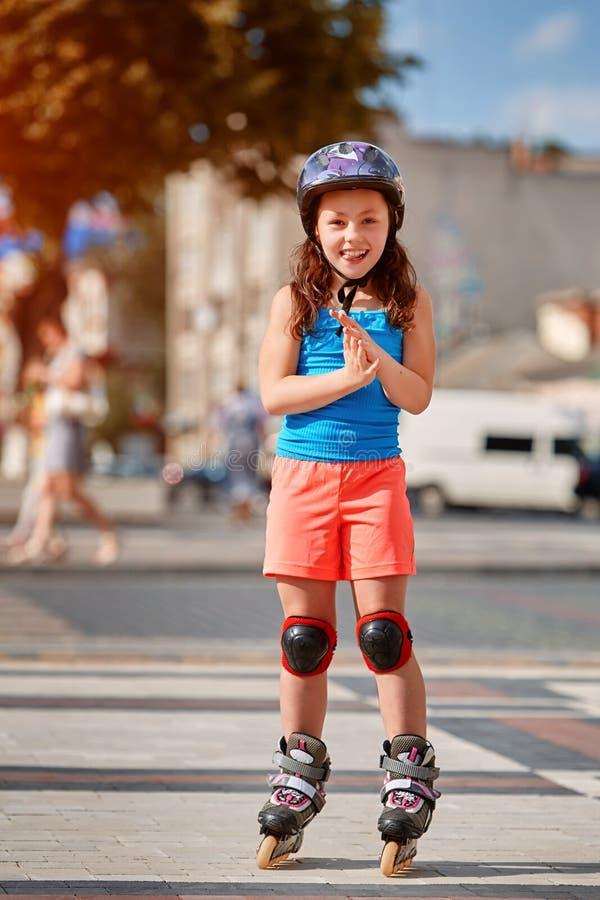 Красивая маленькая девочка стоит в коньках ролика на парке города в sunshiny летнем дне стоковое фото rf