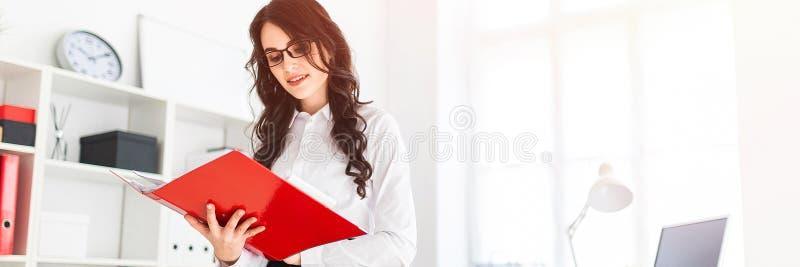 Красивая маленькая девочка стоит в офисе, полагающся на столе и переченях через красную папку с документами стоковые фото