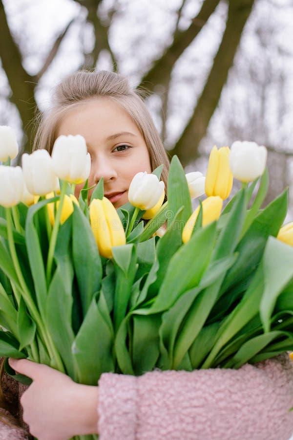 Красивая маленькая девочка с букетом белых и желтых тюльпанов в парке стоковые изображения