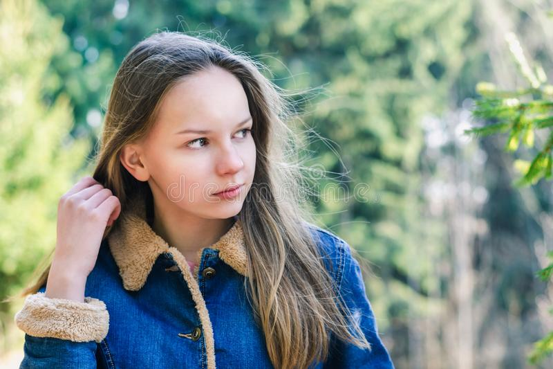 Красивая маленькая девочка с длинными темными светлыми волосами в куртке джинсовой ткани смотрит в расстояние в зеленом парке на  стоковая фотография