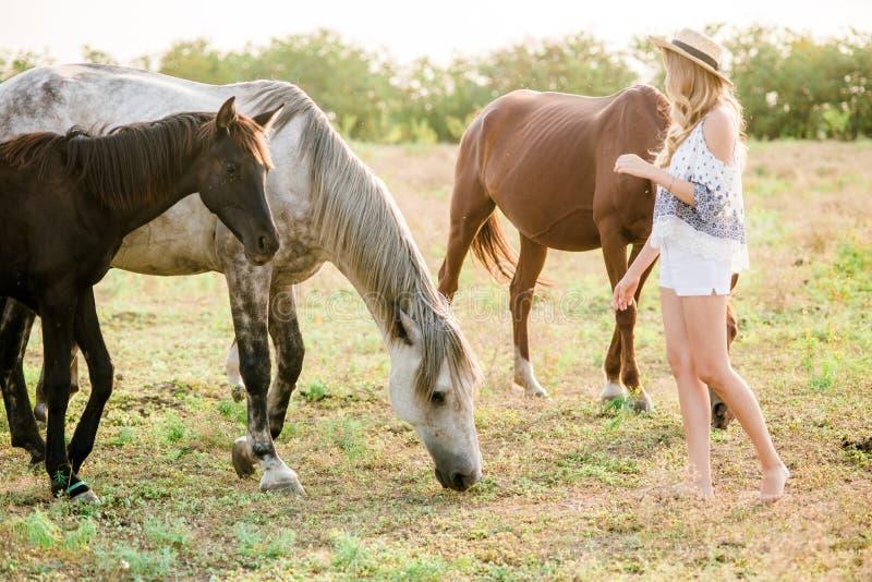 Красивая маленькая девочка, с светлым вьющиеся волосы в соломенной шляпе около лошадей, в сельской местности, теплая осень стоковые фотографии rf