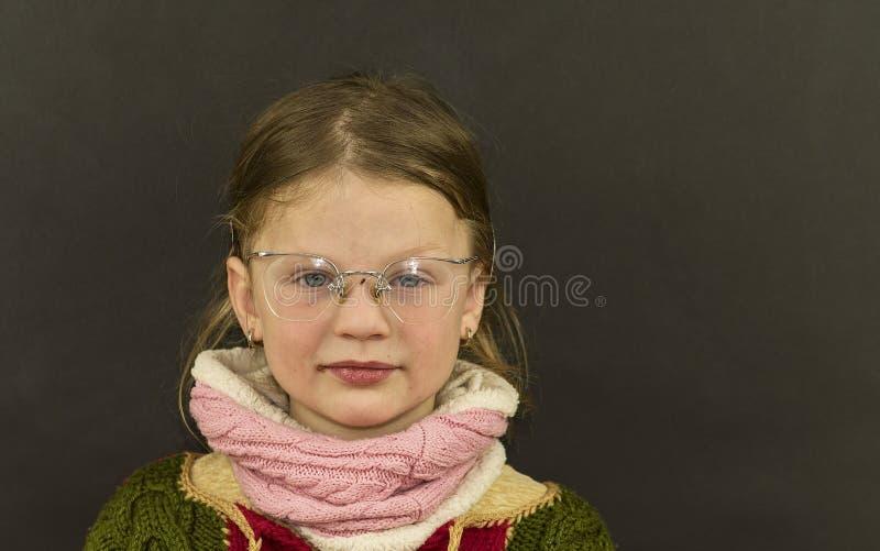Красивая маленькая девочка с стеклами на черной предпосылке Смешная милая девушка с стеклами Малая девушка носит красочный свитер стоковая фотография rf