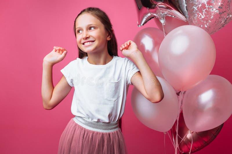 Красивая маленькая девочка, с шариками на розовой предпосылке, празднует день рождения стоковая фотография