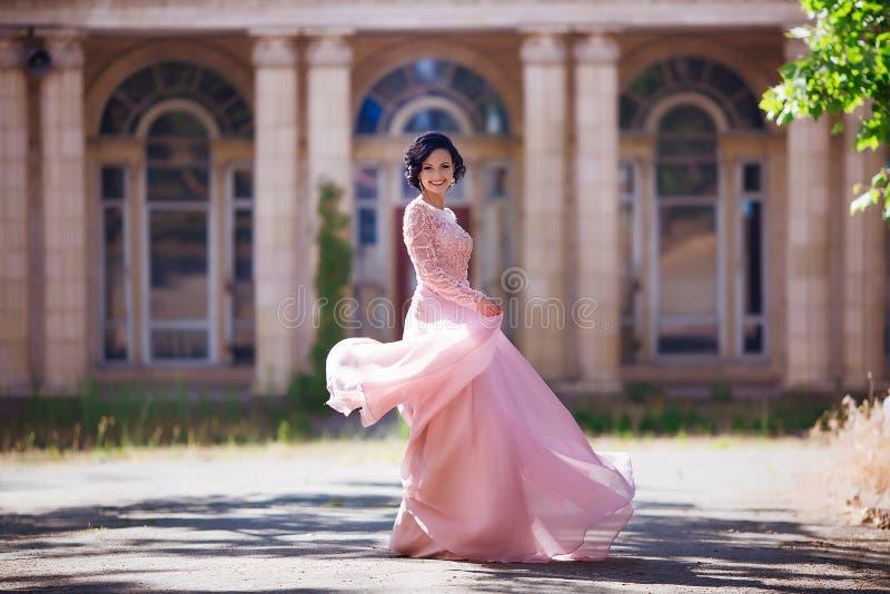 Красивая маленькая девочка с элегантным платьем и славной улыбкой идя в улицу Концепция образа жизни Молодость и счастье стоковые фото