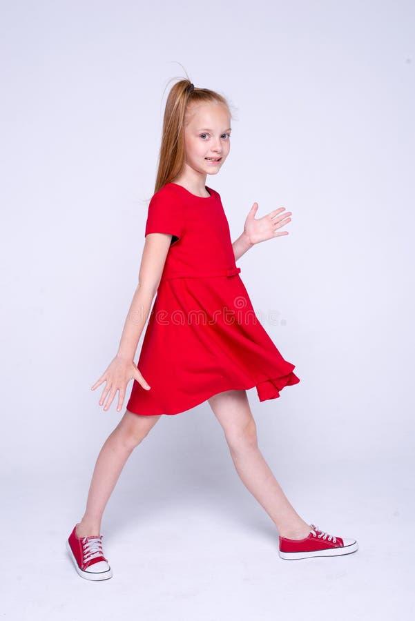 Красивая маленькая девушка redhead в красном платье и тапках представляя l стоковые фотографии rf