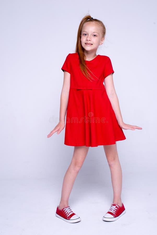 Красивая маленькая девушка redhead в красном платье и тапках представляя l стоковая фотография rf