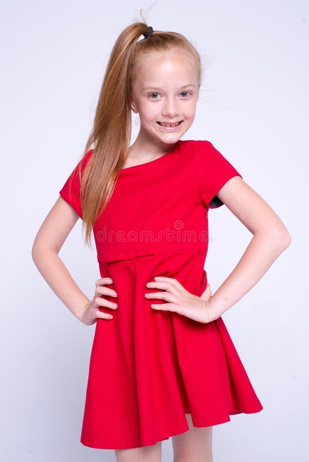 Красивая маленькая девушка redhead в красном платье представляя как модель на белой предпосылке стоковые изображения