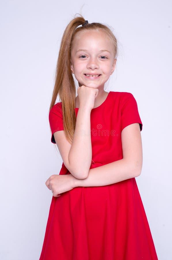 Красивая маленькая девушка redhead в красном платье представляя как модель на белой предпосылке стоковое фото rf