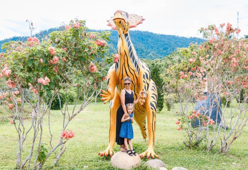 Красивая мама с меньшей дочерью около большого оранжевого динозавра в парке на солнечный день r стоковое изображение
