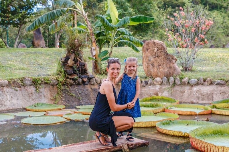 Красивая мама с меньшей дочерью около пруда лотоса в парке на солнечный день стоковое фото rf