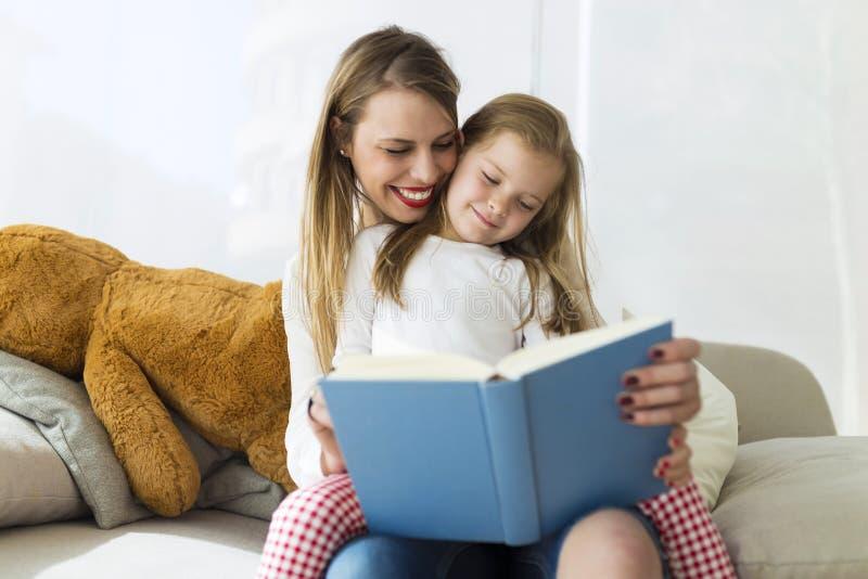 Красивая мать при ее дочь читая книгу дома стоковое изображение