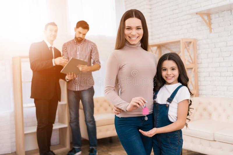 Красивая мать с ее дочерью держит ключи с ключевым кольцом в форме дома стоковое фото