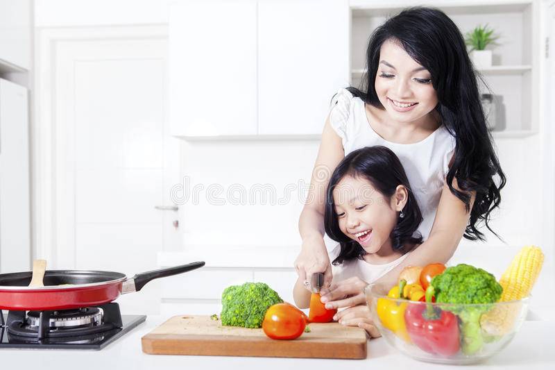 Красивая мать учит, что ее девушка варит стоковое изображение rf