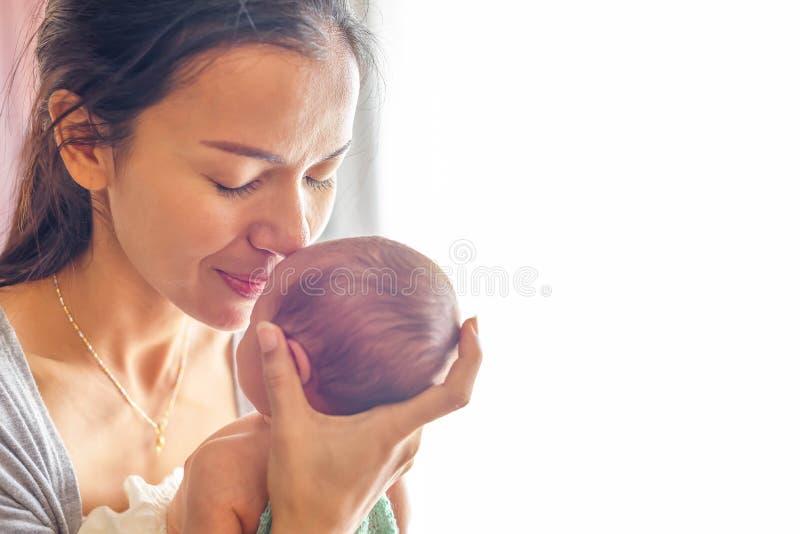 Красивая мать целуя здесь меньшего милого младенца на ее ладони стоковые фотографии rf