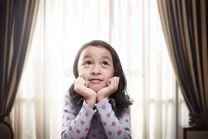 Красивая маленькая азиатская девушка думая и daydreaming на живя r стоковая фотография rf
