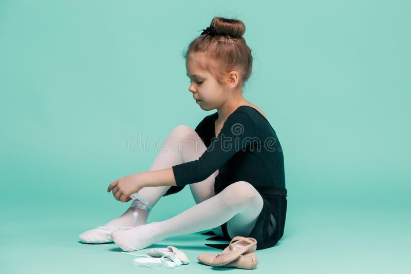 Красивая маленькая балерина в черном платье для танцевать кладущ пешком ботинки pointe стоковые фото