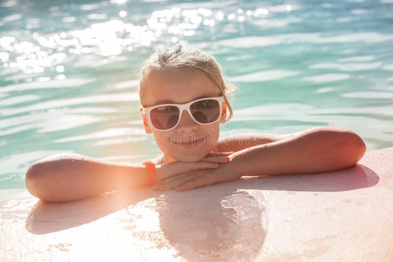 Красивая маленькая белокурая девушка с солнечными очками стоковое изображение