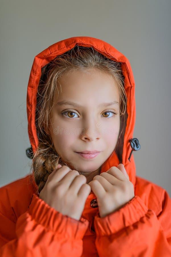 Красивая маленькая девочка в красной куртке с клобуком стоковые изображения rf