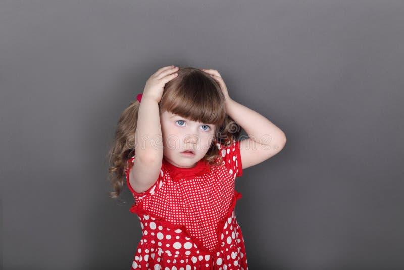 Красивая маленькая девочка в красном платье касается ее голове стоковые изображения rf