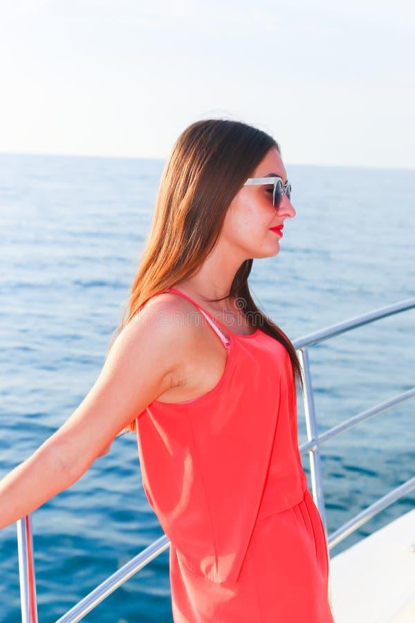 Красивая маленькая девочка в красном платье на яхте стоковые изображения