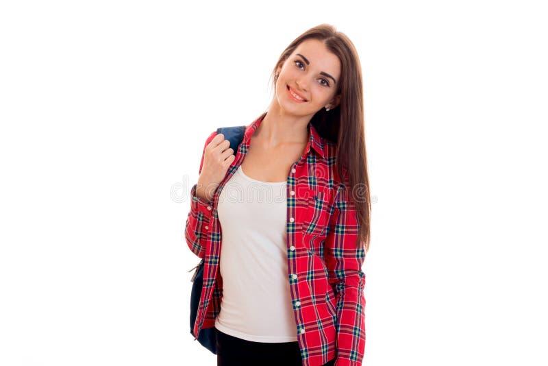 Красивая маленькая девочка в футболке и рубашке держа портфель с плечом и усмехаться стоковое фото
