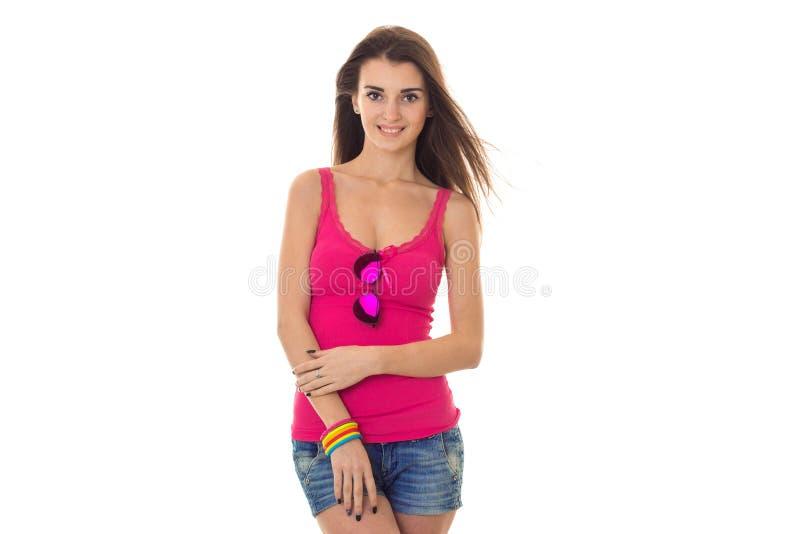 Красивая маленькая девочка в яркой розовой футболке смотрит в камеру и усмехаться стоковое изображение rf