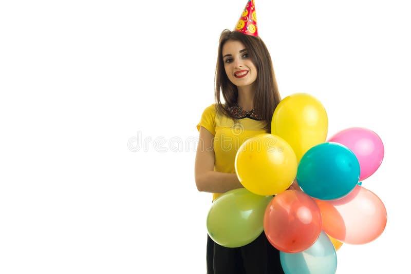 Красивая маленькая девочка держа много воздушные шары с конусом на ее голове и усмехаться стоковая фотография rf