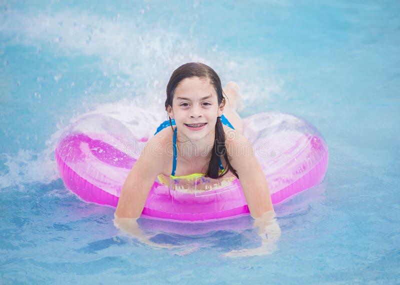 Красивая маленькая девочка играя в бассейне в временени стоковое фото rf