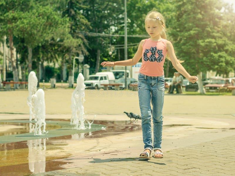 Красивая маленькая девочка идет около фонтана города стоковое изображение