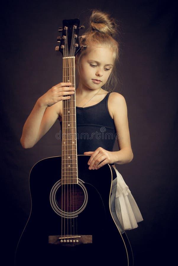 Красивая маленькая девочка стоя и держа гитара стоковое фото rf