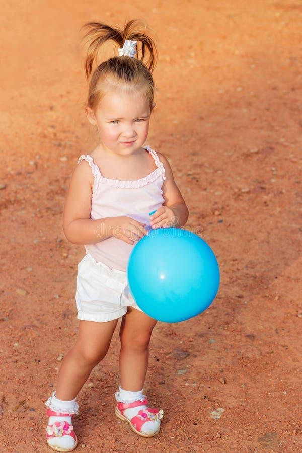 Красивая маленькая девочка стоя с голубым воздушным шаром в парке стоковые изображения