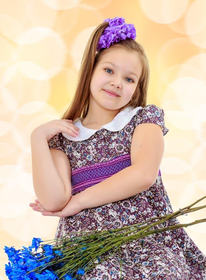 Красивая маленькая девочка с букетом голубых цветков стоковые фотографии rf