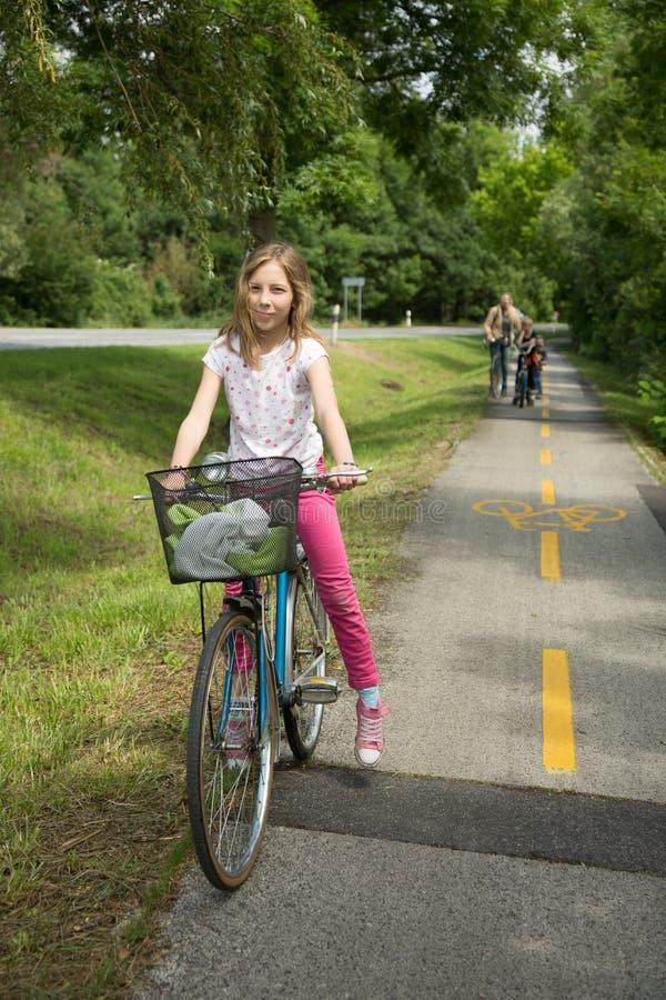 Красивая маленькая девочка с велосипедом внешним стоковое изображение