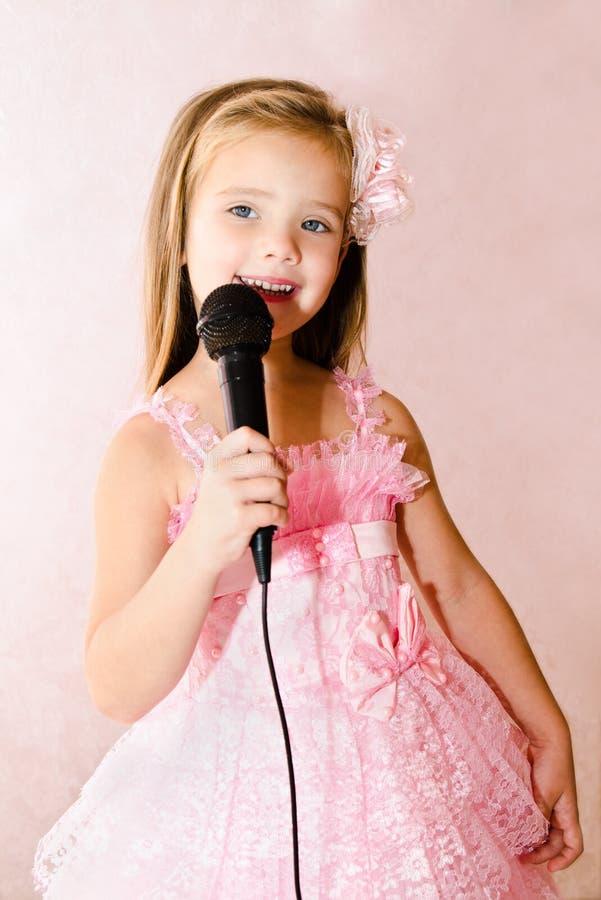 Download Красивая маленькая девочка с микрофоном в платье принцессы Стоковое Фото - изображение насчитывающей радостно, малыш: 33738958