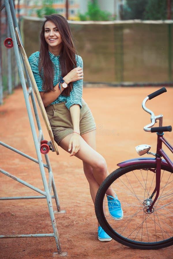 Красивая маленькая девочка с положением longboard и велосипеда стоковые фото