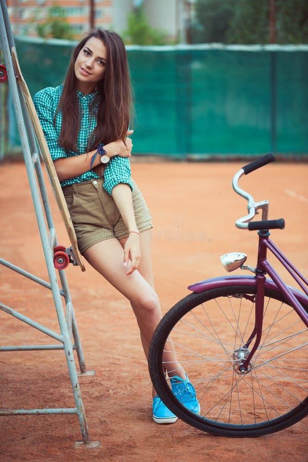 Красивая маленькая девочка с longboard и велосипед стоя на стоковое изображение rf