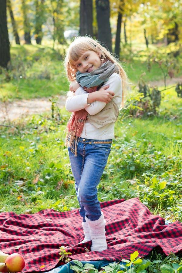 Красивая маленькая длинн-с волосами белокурая девушка стоя в зеленых парке и усмехаться стоковое изображение rf