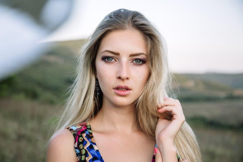 Красивая мечтательная белокурая девушка с голубыми глазами в светлом платье бирюзы лежа на камнях стоковое фото