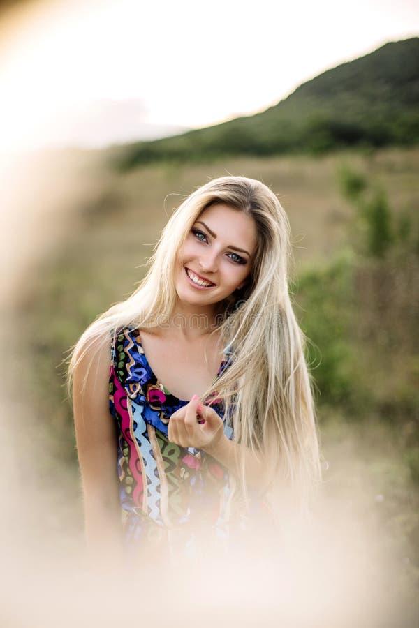 Красивая мечтательная белокурая девушка с голубыми глазами в светлом платье бирюзы лежа на камнях стоковое фото rf