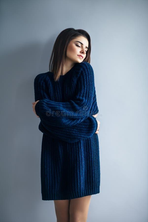 Красивая мечтая девушка в голубом платье обнимая стоковая фотография rf