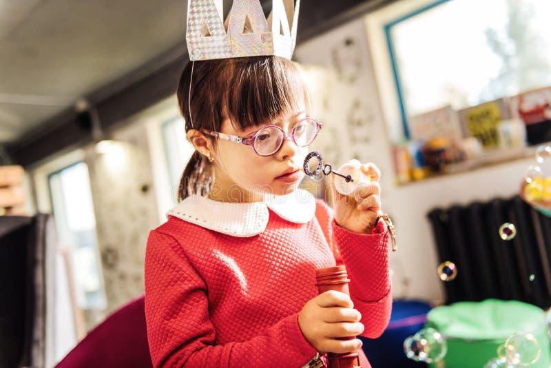 Красивая милая девушка с Синдромом Дауна используя пузыри мыла стоковое фото rf