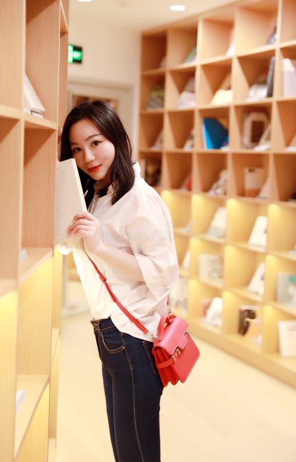 Красивая милая женщина маленькой девочки женщина носит малую красную сумку прочитала книгу на взгляде модели библиотеки книжного  стоковое фото rf