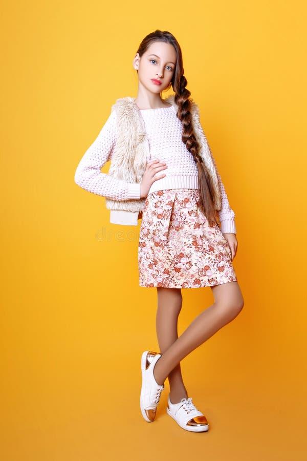 Красивая милая девушка моды подростковая в свитере и skir на желтой предпосылке с длинный представлять волос стоковое фото rf