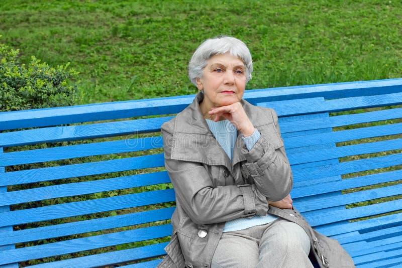 Красивая милая пожилая женщина сидя на сини скамейки в парке стоковые фотографии rf